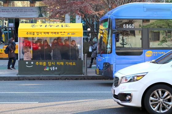 서울 성동구청 앞 버스정류장에 설치된 '온기누리소'. 최강 한파가 찾아온 12일 아침 버스를 기다리는 시민들이 텐트 안에서 추위를 피하고 있다.[사진 성동구청]