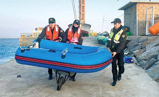 평택해경 안산파출소 직원들이 손수레에 고무보트를 싣고 부두로 이동하고 있다. [사진 해양경찰청]