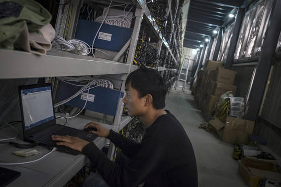In this Sept. 28, 2016, photo, a man sets up a new bitcoin mining machine to connect to the internet at a bitcoin mine built beside a hydropower station in a remote valley in Aba prefecture in southwestern China's Sichuan province. The launch of a U.S. futures contract for bitcoin on Sunday, Dec 10, 2017, underscores the virtual currency's increasing mainstream acceptance, including in many parts of Asia, where it already has a wide following among speculators and investors. (Chinatopix via AP) <저작권자(c) 연합뉴스, 무단 전재-재배포 금지>