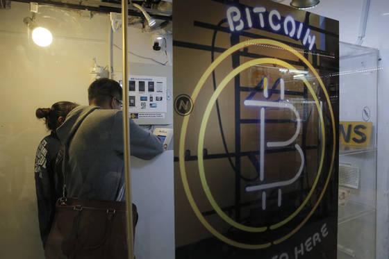 비트코인 등 암호화폐 투자 열기는 한국, 중국, 홍콩 등 동아시아가 가장 뜨겁다. 홍콩에 있는 한 비트코인 ATM기기를 투자자들이 사용하고 있다. [홍콩 AP=연합뉴스]