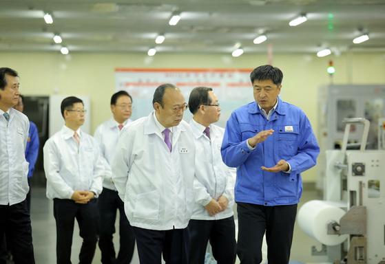 김승연 한화그룹 회장(오른쪽 셋째)이 지난 11일 중국 장쑤성 난퉁시 한화큐셀 치둥 공장을 방문해 현지 공장장인 김상훈 전무(오른쪽 첫째)에게 태양광 모듈 생산에 대한 설명을 듣고 있다. [사진 한화그룹]