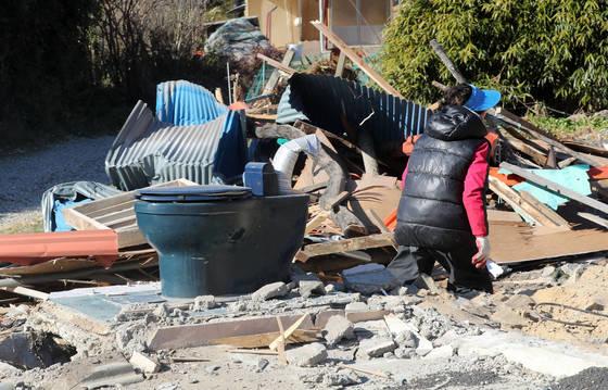 13일 오후 지진으로 피해를 본 경북 포항시 북구 흥해읍 한 주택에서 인근 주민이 철거 잔해를 정리하고 있다. [연합뉴스]