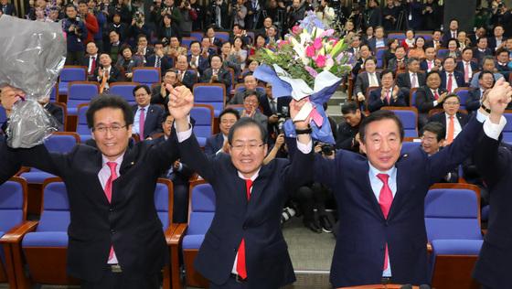 """자유한국당은 12일 오후 국회에서 의원총회를 열고 신임 원내대표에 김성태 의원(오른쪽)을 선출했다. 김 원내대표는 당선소감을 통해 '문재인 정권의 독단과 전횡을 막는 데 앞장서겠다""""며 대여 투쟁의지를 밝혔다. 김 원내대표, 홍준표 대표, 함진규 신임 정책위의장(오른쪽부터)이 기념촬영을 하고 있다. [박종근 기자]"""