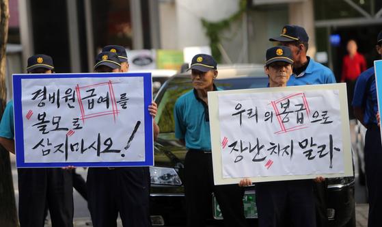 9월 15일 대전의 한 아파트 입구에서 이 아파트 경비원과 청소노동자, 시설관리직 관계자들이 '우리의 급여를 볼모 삼지 말라'는 피켓 시위를 하고 있다. [연합뉴스]