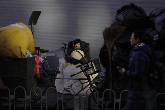 지난달 15일 중국 베이징의 한 재활용 쓰레기센터에서 환경미화원 여성이 강추위 속에서 이불을 덮은 채 쉬고 있다. [베이징 AP=연합뉴스]