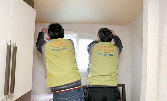 동아쏘시오홀딩스 임직원이 동대문구의 혼자 사는 어르신들 집을 방문해 단열뽁뽁이 시공 봉사를 하고 있다. [사진 동아쏘시오그룹]