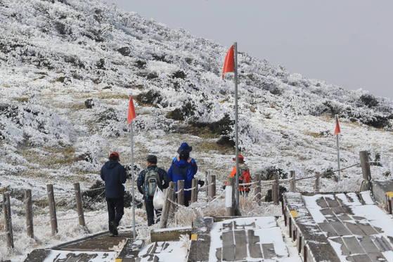 안전한 겨울 산행을 위해서는 기상정보 확인 등 철저한 준비가 필요하다. 사진은 지난달 19일 오전 제주 한라산 윗세오름 대피소에서 탐방객들이 눈꽃이 활짝 핀 탐방로를 걷고 있는 모습 [연합뉴스]