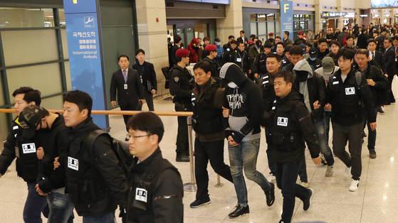 항공기로 집단 송환된 범죄 피의자들이 인천공항을 통해 입국하고 있다. 모자와 마스크로 얼굴을 가린 피의자들을 경찰관들이 양쪽 옆에 붙어 호송했다. [연합뉴스]