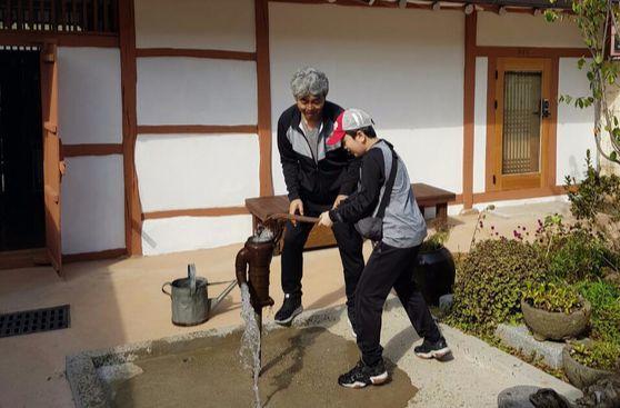 공주 하숙마을을 찾은 남성이 아들과 함께 마당에 있는 펌프에서 물을 퍼내고 있다. [사진 공주 하숙마을]