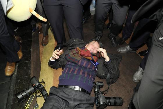 14일 오전 문재인 대통령 국빈방문 행사를 취재하던 한국의 한 사진기자가 베이징 국가회의 중심 B홀에서 중국 측 경호 관계자에게 일방적으로 폭행 당해 쓰러져 있다. '한·중 경제·무역 파트너십 개막식 '에서 스타트업관 이동 중에 폭행당했다. [연합뉴스]