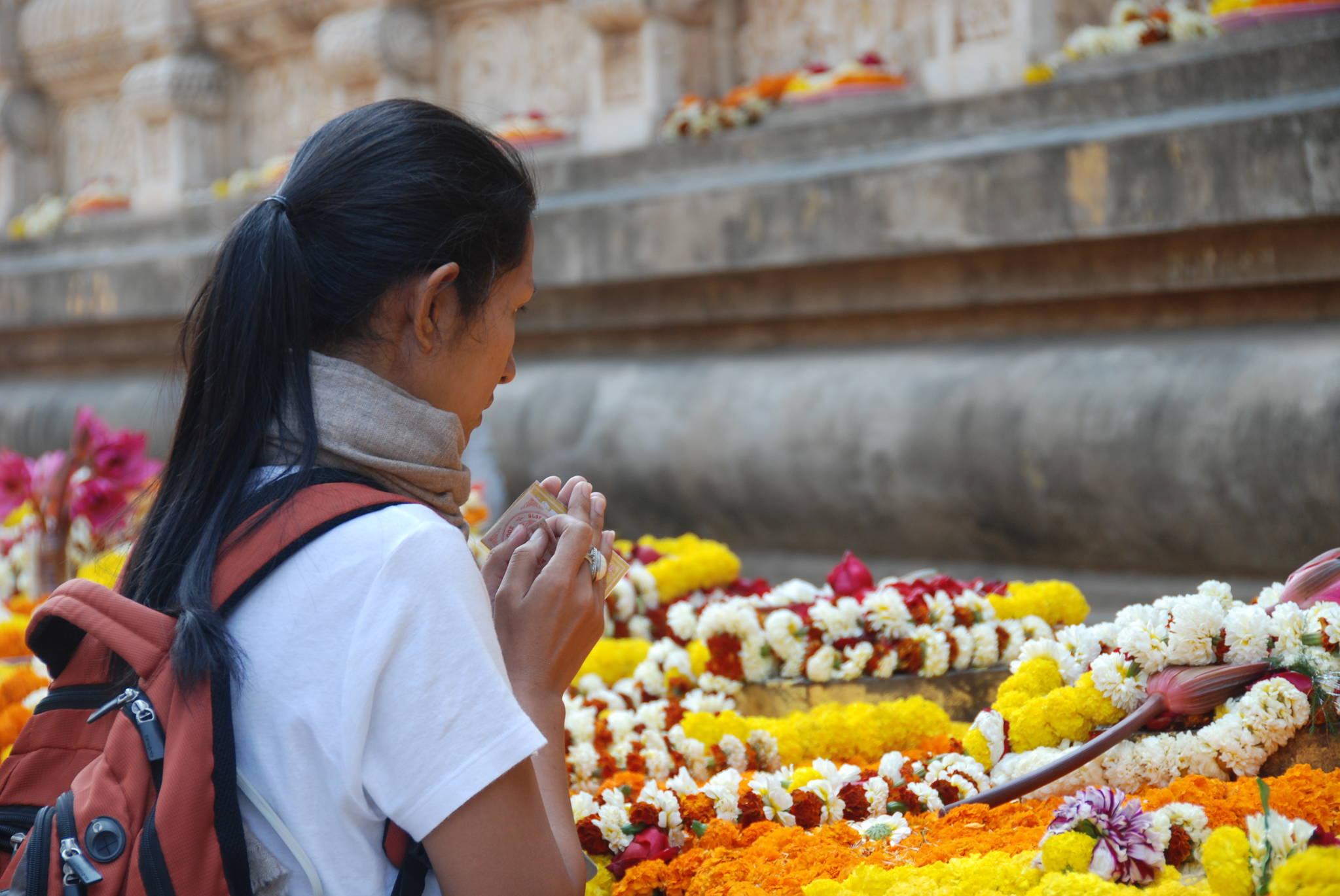보드가야 사원의 대탑 앞에서 한 순례객이 두 손을 모으고 있다. 그의 앞에는 꽃을 꿰어 만든 꽃목걸이가 놓여 있다. 남방 불교에서는 꽃으로 붓다에게 공양하는 전통이 있다.