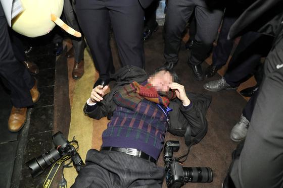 중국 경호원들이 14일 베이징에서 열린 '한·중 경제무역 파트너십 개막식'에서 문재인 대통령을 취재 중이던 한국 사진기자를 밀어 넘어뜨리고 또 다른 기자를 폭행하고 있다. [연합뉴스]