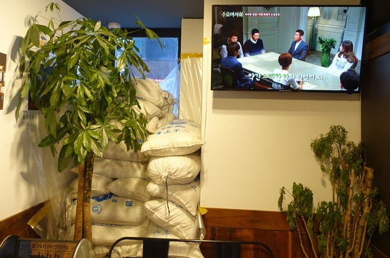 """교대점 출입구에 쌓아둔 천일염 자루. '육통령'은 저렇게 9년간 간수를 뺀 소금을 쓴다. 옆 TV화면에는 '육통령'을 '바삭한 껍질! 지례 흑돼지 오겹살집""""이라고 소개하는 케이블 채널 tvN의 '수요미식회' 방송 내용이 흐르고 있다."""