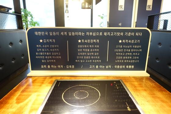 교대점의 테이블 사이 칸막이 장식. '요리 좀 하는 여자-김옥경/고기 좀 아는 남자-국중성'이라는 문구에서 주인 부부의 음식에 대한 열정과 자신감이 읽힌다.