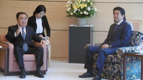 문재인 대통령의 일본 특사인 문희상 더불어민주당 의원(왼쪽)이 5월 18일 오전 도쿄 총리 관저에서 아베 신조 총리를 만나 대화를 나누고 있다. 당시에도 문 의원이 더 작은 의자에 앉아 있다. [사진 주일한국대사관]