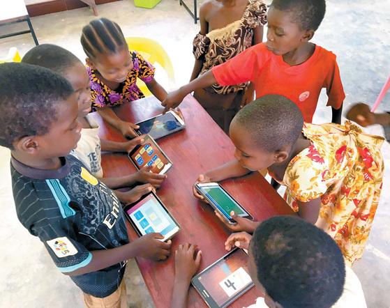 탄자니아 아이들이 에 누마의 교육 앱 '킷킷스 쿨'을 사용해 공부하고 있다.