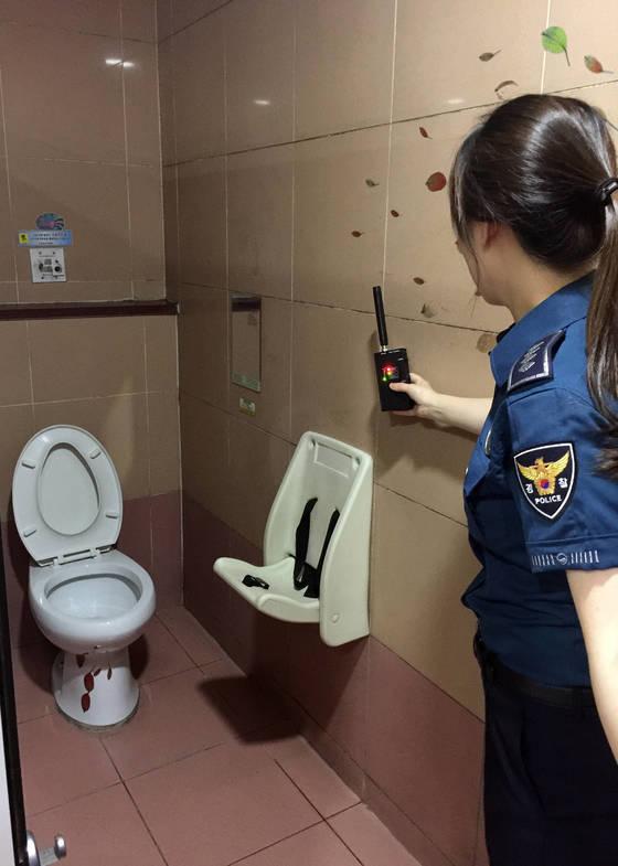 지난 9월 21일 광주 서구 치평동 지하철 상무역 공중화장실에서 경찰관이 전파탐지기로 '몰카' 설치 여부를 확인하고 있다. [연합뉴스]