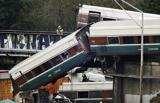 18일(현지시간) 오전 미국 워싱턴 주 시애틀 남쪽 듀폰에서 암트랙 열차가 탈선, 고속도로 위에 위험스럽게 매달려 있다.[AP=연합뉴스]