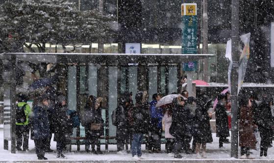 눈이 내린 18일 오전 광화문 정류장에서 시민들이 버스를 기다리고 있다. [연합뉴스]