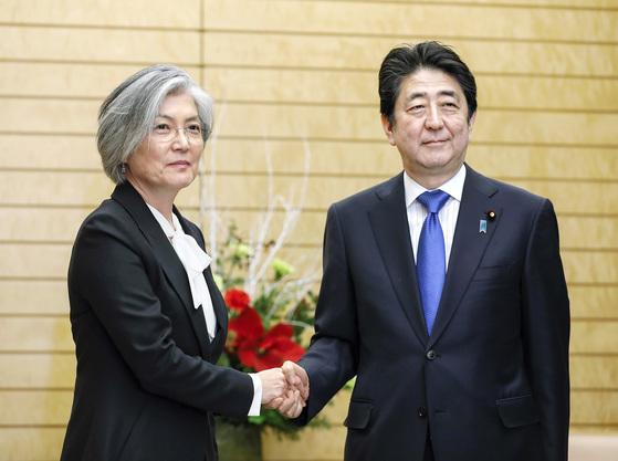 강경화 장관(왼쪽)이 19일 일본 도쿄 총리관저에서 아베 신조 총리를 만나 악수하고 있다. 강 장관은 아베 총리에게 '평창 겨울올림픽에 참석해 달라'는 문재인 대통령의 메시지를 전달했다. [AP=연합뉴스]