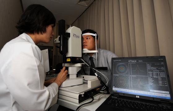 30대 남성 환자가 각막 검사를 받고 있다. 평소 불편을 느낄 만큼 눈이 뻑뻑하고 충혈이 잘되면 안구건조증일 수 있으므로 안과 검진을 받는 게 좋다. [사진 세브란스병원]
