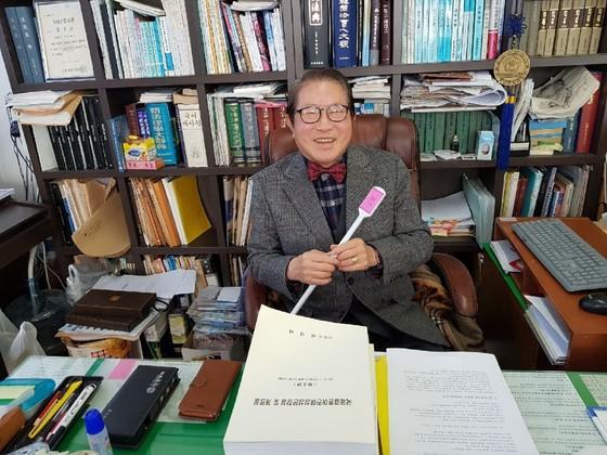 법무사 배선위씨가 사무실에서 자신이 개발한 효자손을 들고 활짝 웃고 있다. 김방현 기자
