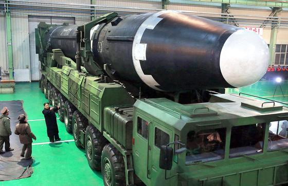 김정은 북한 노동당 위원장(왼쪽 아래쪽)이 이동식발사대(TEL)에 실린 대륙간탄도미사일(ICBM)급 화성-15형를 보며 말하는 모습. [노동신문=연합뉴스]