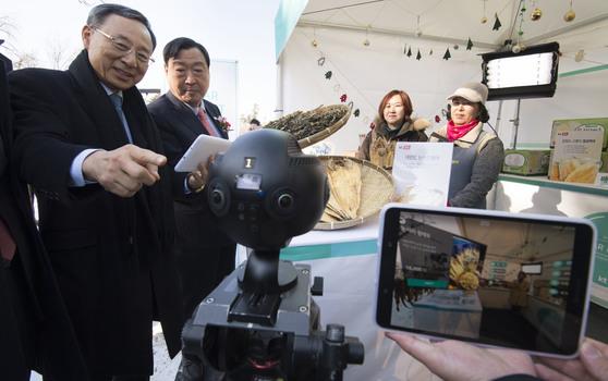 황창규 KT 회장(왼쪽)과 이희범 평창동계올림픽 조직위원장(왼쪽에서 두번째)이 20일 강원도 대관령 의야지마을에서 360도 가상현실(VR) 카메라를 활용해 장보기 체험을 하고 있다. [우상조 기자]