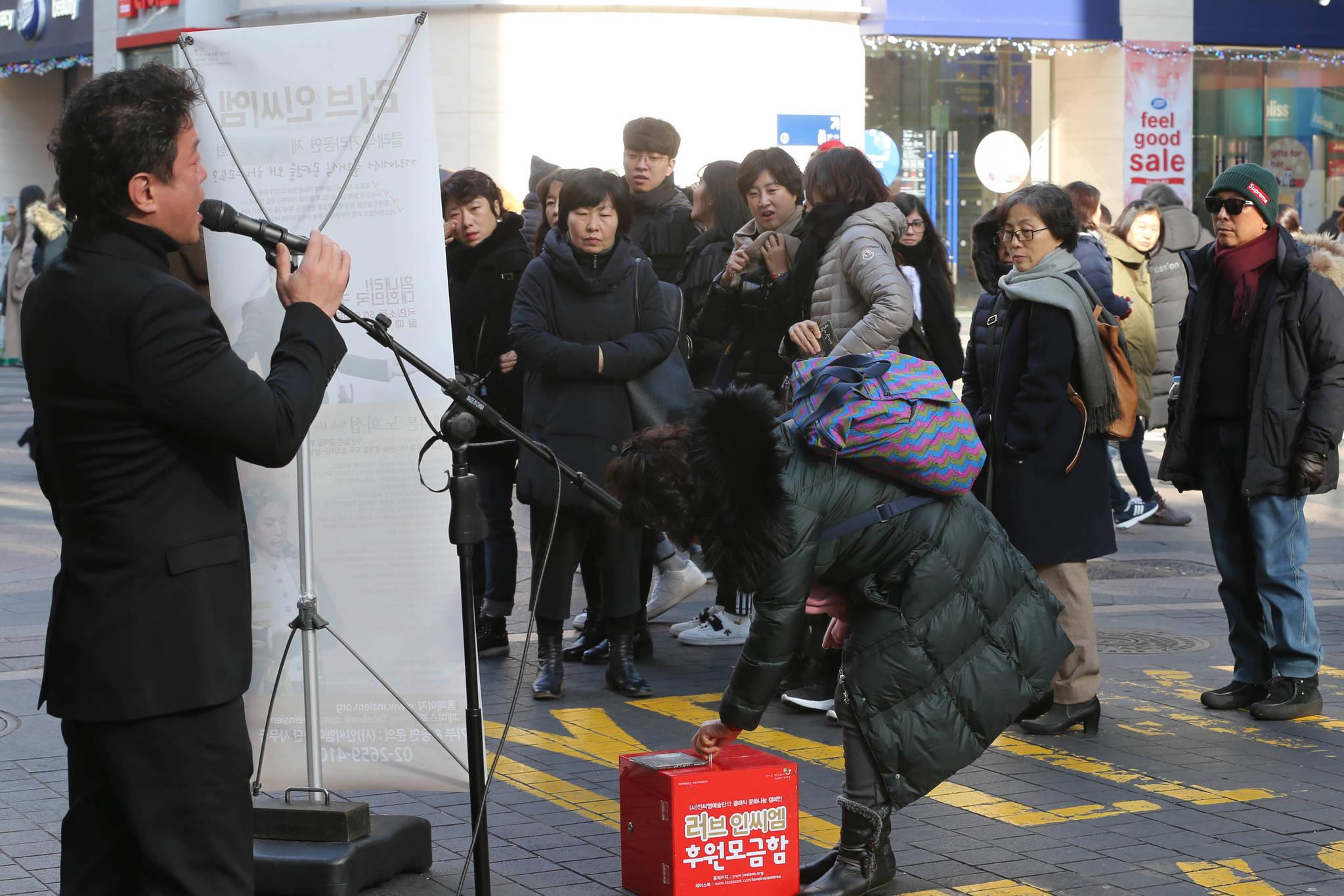 노래를 듣던 한 시민이 모금함에 돈을 넣고 있다. 신인섭 기자
