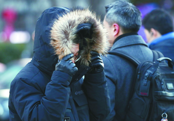 서울 아침기온 영하 7도의 매서운 추위가 찾아온 지난 11일 오전 두꺼운 옷차림을 한 출근길 시민들이 광화문 네거리를 지나고 있다. 내년 1월에는 기온이 평년과 비슷하거나 낮겠고, 일시적인 강추위가 닥칠 수도 있다고 기상청이 예보했다.[연합뉴스]