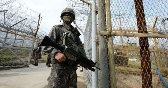 2015년 8월 비무장지대(DMZ)에서 발생한 지뢰폭발사고 현장 주변에서 장병들이 무장한 채 수색작전을 하고 있다. [사진 국방부]