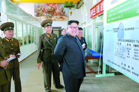 북한 김정은이 지난 8월 국방과학원 화학재료연구소를 찾아 '4D탄소/탄소복합재료' 공정을 나열한 설명판 앞에 서 있다. [연합뉴스]