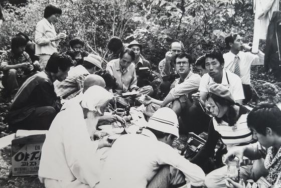 1975년10월3일, 장준하 선생 실족한 포천 약사봉 답사현장 사진. 김사복 씨와 힌츠페터 기자가 나란히 앉아있고, 사진 왼쪽편에 흰옷에 흰머리의 함석헌 선생이 앉아있다. [김사복의 아들 김승필 제공]