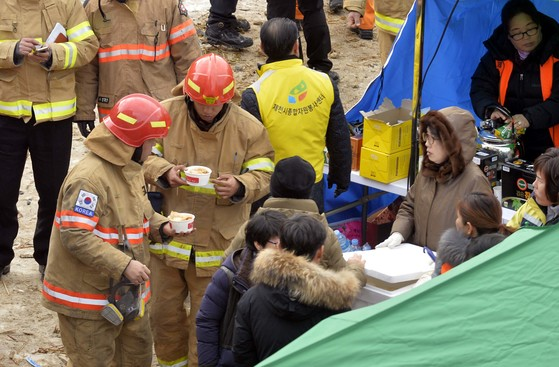 29명이 숨지는 대형 참사가 발생한 충북 제천시 하소동 소재 8층 건물 스포츠센터에서 22일 오후 화재진압을 마친 소방관들이 뒤늦은 식사를 하고있다. [프리랜서 김성태]