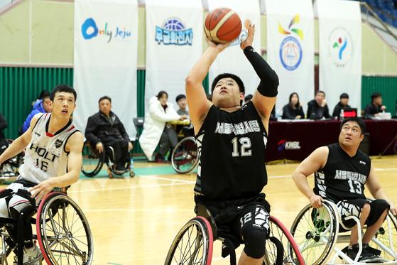 사고로 오른쪽 다리를 잃고 휠체어 농구를 시작한 양동길 선수가 골밑에서 슛을 시도하고 있다.