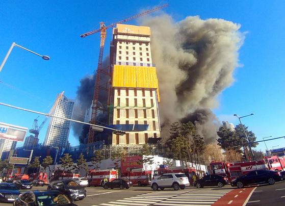 지난 25일 오후 경기도 수원시 영통구 광교 SK건설 공사장에 화재가 발생해 소방관들이 진화작업을 벌이고 있다. 이번 화재로 16명의 사상자가 발생했다. [연합뉴스]