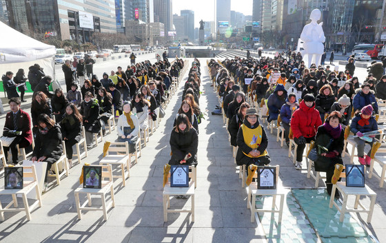 올해 마지막 '수요시위'가 27일 서울 중학동 옛 주한일본대사관 앞에서 열렸다. 집회 뒤 광화문광장까지 행진한 참가자들이 올해 돌아가신 8명의 위안부 피해자 할머니를 추모하는 행사를 하고 있다. [강정현 기자]