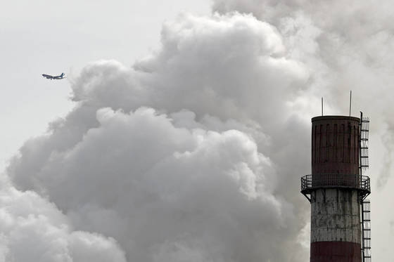 지난달 13일 중국 베이징의 석탄화력발전소에서 뿜어져 나오는 연기와 수증기 너머로 여객기 한 대가 지나가고 있다. [AP=연합뉴스]