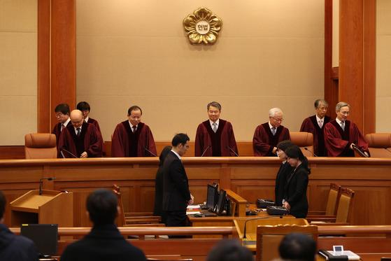이진성 헌법재판소장 등 재판관들이 28일 오후 서울 종로구 헌법재판소 대심판정에서 자리에 착석하고 있다. 우상조 기자