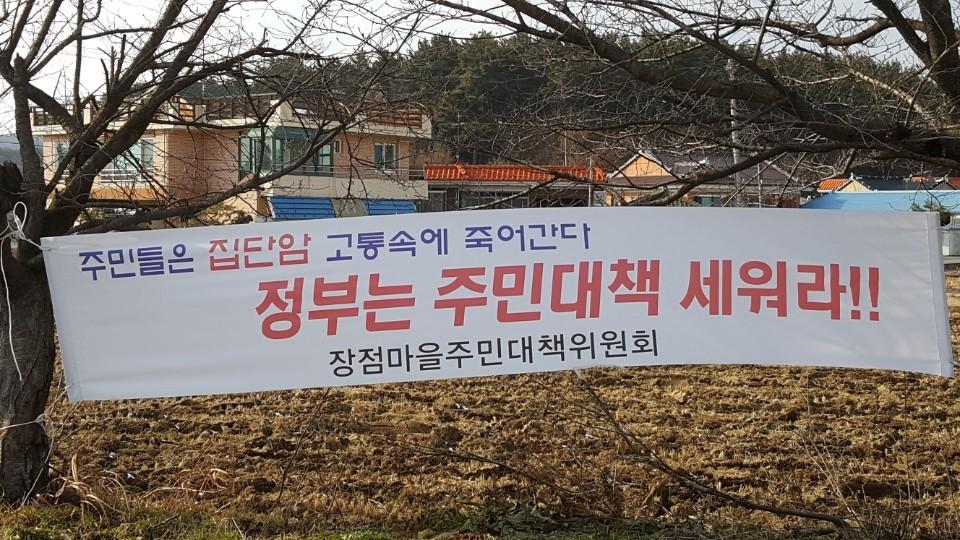 전북 익산시 장점마을에 주민들이 설치한 플래카드. 집단 암 발생 피해에 대한 대책를 요구하는 내용이다. [사진 환경안전건강연구소]