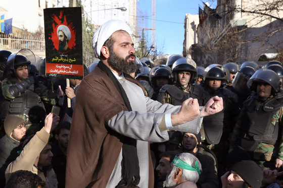[Mideast Iran Saudi Arabia Protes]Surrounded by policemen, a Muslim cleric addresses a crowd during a demonstration to protest the execution of Saudi Shiite Sheikh Nimr al-Nimr, seen in poster, in front of the Saudi embassy in Tehran, Iran, Sunday, Jan. 3, 2016. Saudi Arabia announced the execution of al-Nimr on Saturday along with 46 others. Al-Nimr was a central figure in protests by Saudi Arabia's Shiite minority until his arrest in 2012, and his execution drew condemnation from Shiites across the regio