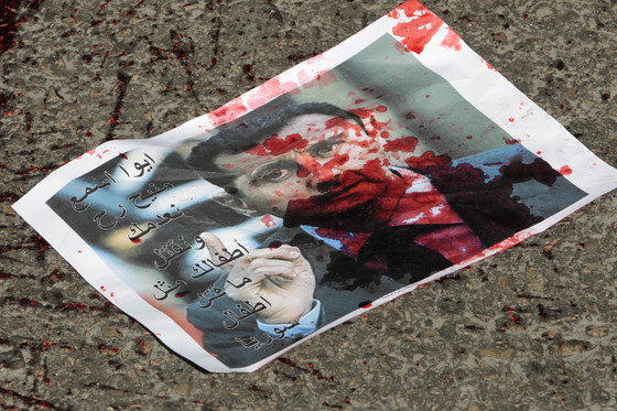 """[Mideast Lebanon Syri]A leaflet negatively depicting Syrian President Bashar Assad with Arabic words reading: """"hey listen well, we will execute you and kill your child same like you killed the Syrian children,"""" is seen on the ground near anti-Syrian regime protesters and supporters of the Islamic group Jamaa Islamiya, during a demonstration where a number of Assad supporters were also protesting, in front the Russian embassy, in Beirut, Lebanon, on Sunday, Feb. 5, 2012. Russia and China vetoed a U.N. Secur"""