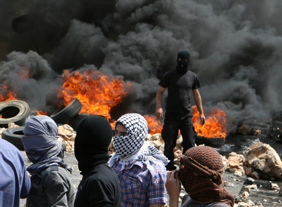 [LEBANON]Lebanese Sunni Muslim men, with faces covered, stand, after they burnt tyres to block a road to protest the killing of Sheikh Ahmed Abdul Wahid, a Sunni Muslim cleric, and Muhammed Hussein Miraib, both members of the Lebanon-based March 14 political alliance, in Jeb Jennin, West Bekaa May 21, 2012. Lebanese soldiers shot dead two members of an alliance against Syrian President Bashar al-Assad in northern Lebanon on Sunday, security sources said, in the latest incident to raise fears Syria's turmoi