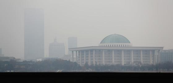 30일 수도권 지역에 처음으로 미세먼지 비상저감 조치가 발령될 전망이다. 전국 대부분 지역에 비가 내린 지난 24일 미세먼지와 짙은 안개가 겹쳐 서울 국회의사당 뒤편 건물이 뿌옇게 보인다. 우상조 기자
