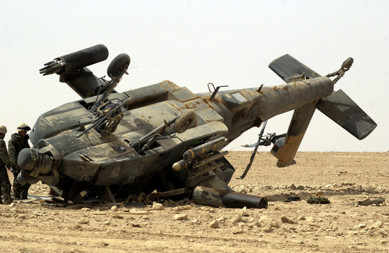 An inspection team examines a US Army (USA) AH-64 Apache helicopter that crashed during landing at Tactical Assembly Area SHELL, in Central Iraq. The helicopter is assigned to A/Company 2-101st Aviation Regiment, and was operation in support of Operation IRAQI FREEDOM.