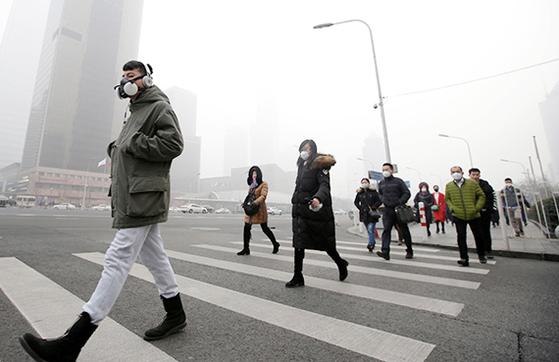 스모그가 가득한 중국 베이징의 거리에서 방독면처럼 생긴 마스크를 착용한 시민이 횡단보도를 지나고 있다. [로이터=연합뉴스]