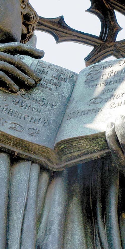 """독일 비텐베르크에 세워진 루터 동상. 손에 든 독일어 성경에는 독일식 프락투어체가 새겨져 있다. 왼쪽 면에서 구약이 끝나고, 신약이 시작되는 오른쪽 면에는 다음과 같은 내용이 담겼다. """"Das Neue Testament verdeutscht von Doktor Martin Luther(마르틴 루터 박사가 독일어로 옮긴 신약성서)"""" [중앙포토]"""