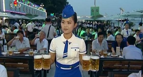"""지난해 평양 대동강맥주 축전에서 여직원이 맥주를 나르는 모습. 영국 이코노미스트는 """"북한 대동강맥주가 한국 맥주보다 맛있다""""고 평가하기도 했다. [조선중앙통신]"""
