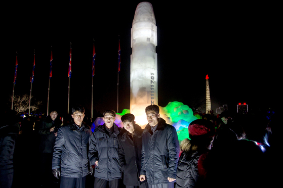 북한 주민들이 지난해 12월 31일 평양 김일성광장에서 열린 새해맞이 평양 얼음조각 축제장을 관람하고 있다. 뒤로 얼음으로 조각된 대륙간탄도미사일(ICBM) 화성-15형이 보인다. [AFP=연합뉴스]