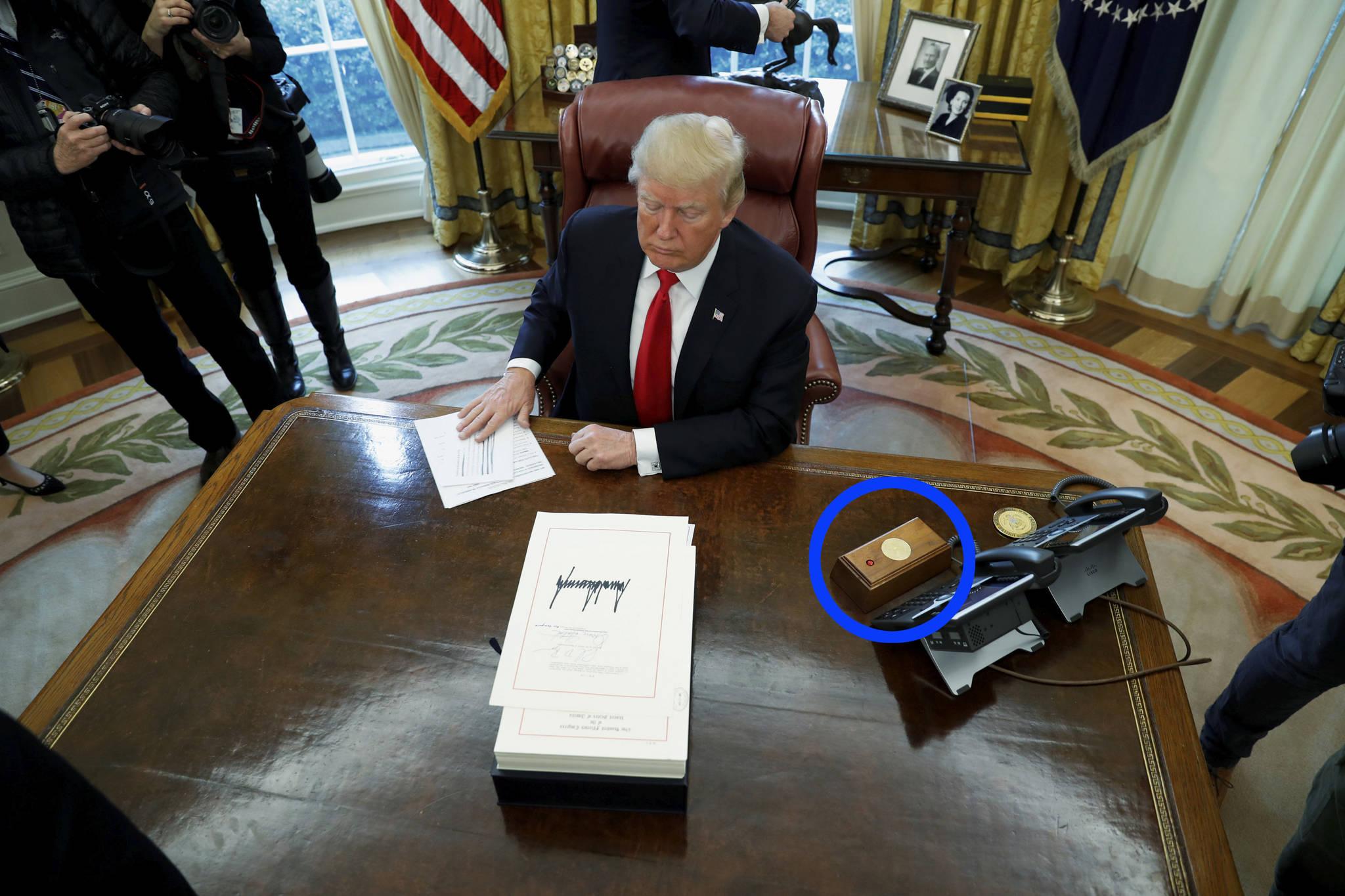 도널드 트럼프 미국 대통령이 지난해 12월 22일 대통령 집무실에서 종합적인 감세 정책에 사인하고 있다. 트럼프 대통령 오른쪽에 빨간 단추가 있는 조그마한 박스가 보인다. [로이터=연합뉴스]